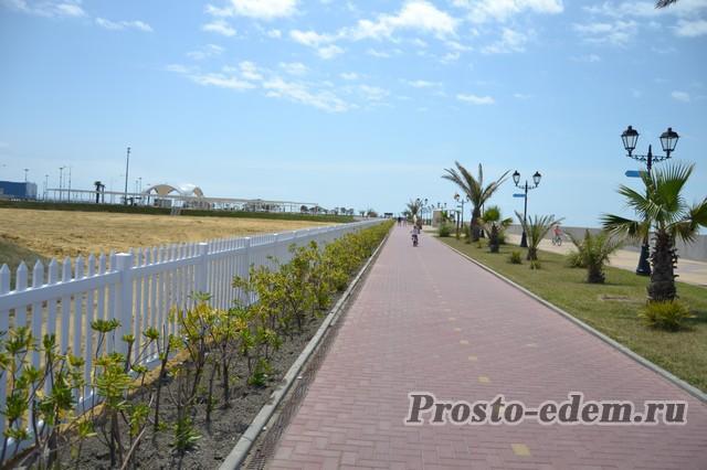 Слева от дорожки песочный пляж в Сочи около олимпийского Парка